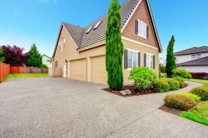 clapboard siding house with two car garage and driveway. view of green beautiful landscape