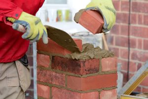 a builder lays the first brick