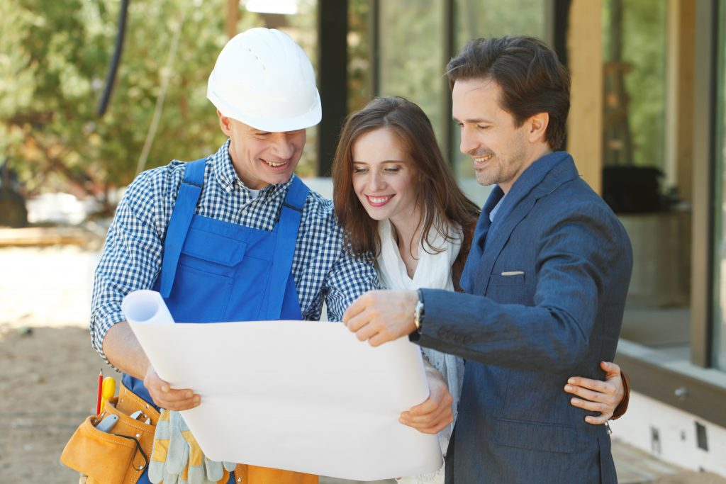 3 home owners looking at plans on how to build a house