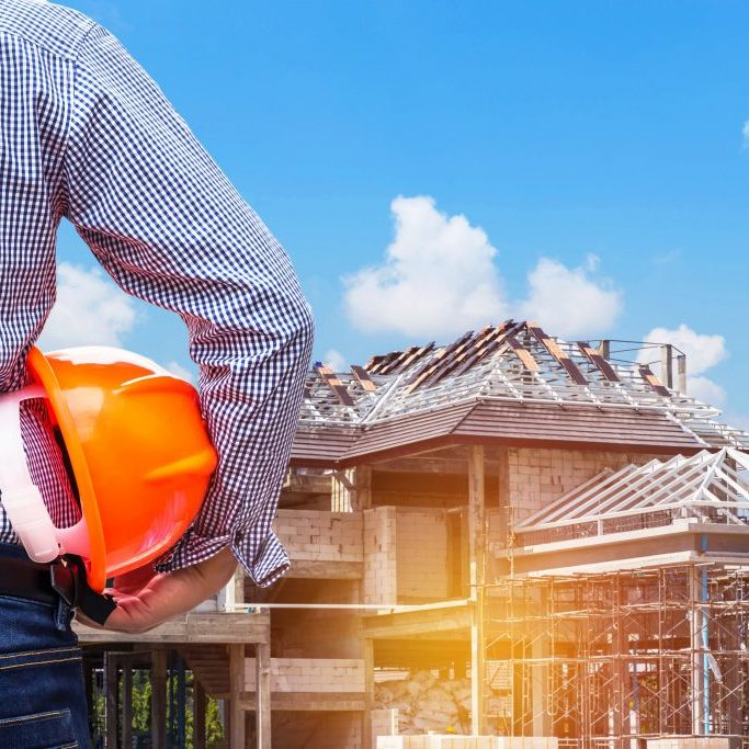 a building contractor holding hard hat looking at a building construct